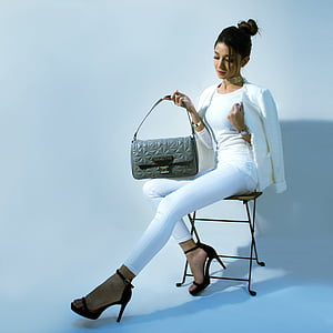 woman in white jeans and shirt holding grey leather handbag