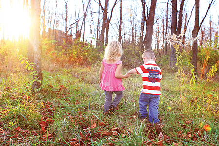 boy and girl walking on grass field