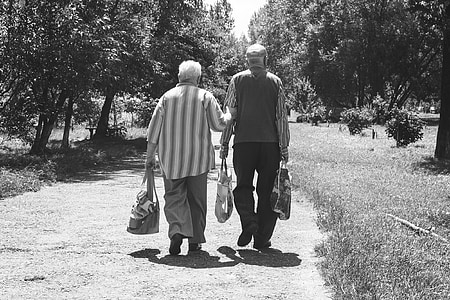 grayscale photo of man and woman walking on dirt road