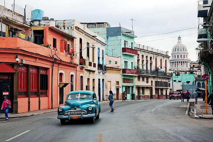 blue car near concrete buildings at daytime