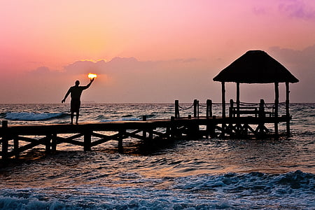 photo of man on dock during golden hour