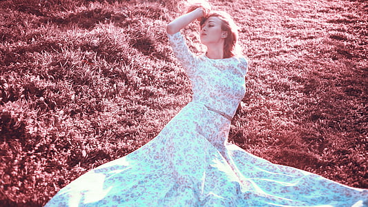 woman wearing white and pink floral 3/4 sleeved crop top and skirt laying on grass field