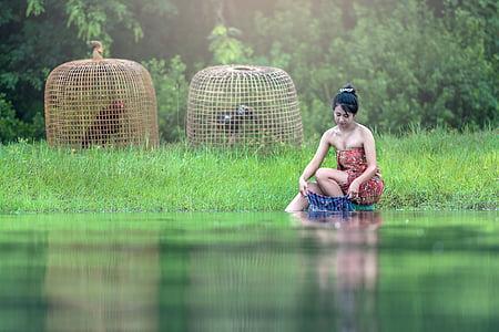 woman washing clothes on lake