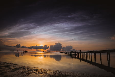 sunset on body of water with dock