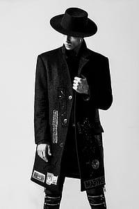 man wearing black long coat and black hair