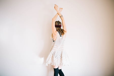 woman wearing white sleeveless dress lifting her both hands