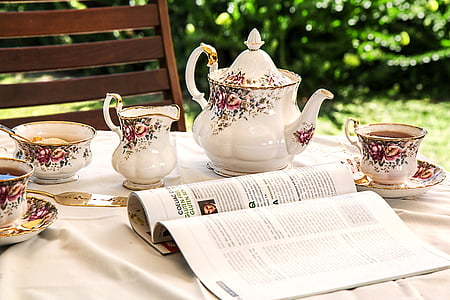 open magazine near white-and-pink floral tea set on top of table
