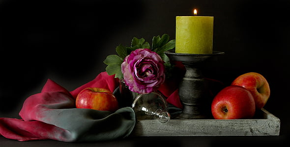 red apples beside gray candlestick
