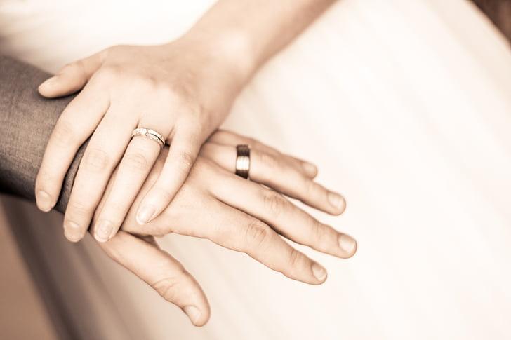 man and woman wearing wedding rings