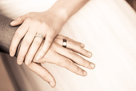 man and woman wearing wedding rings