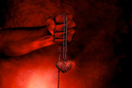 person holding red heart pendant necklace