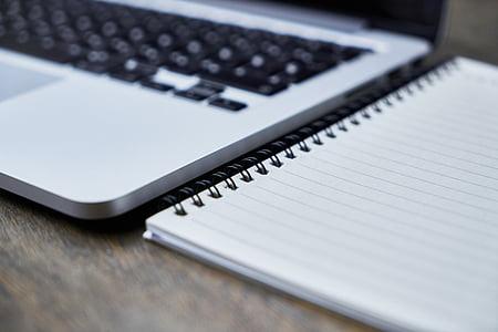 notebook near laptop