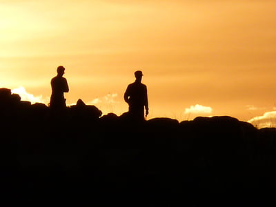 silhouette of two people on top of hill