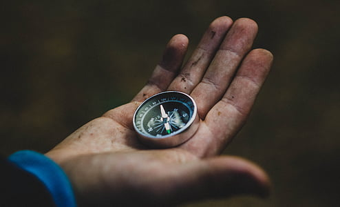 person holding black compass