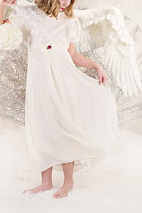 girl wearing white dress and wings standing on white rug