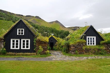 two black painted houses across green mountain