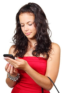 woman in red tube top holding Android smartphone