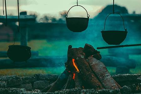 three pots hanged near campfire during dawn