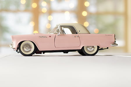 person taking photo of pink and white convertible coupe die-cast model