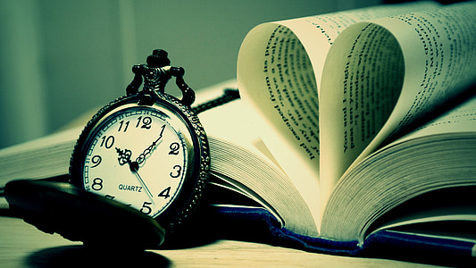 black and white pocket watch leaning on book