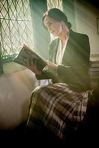 woman wearing black formal coat reading book