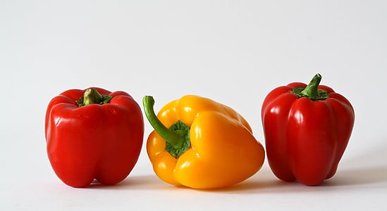 macro shot of two red and one yellow bellpeppers