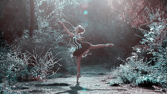 woman in black and white dress dancing in forest during daylight