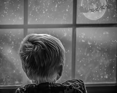 grayscale photo of boy leaning on window looking at moon during nighttime