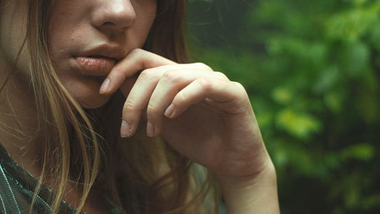 selective focus photography of woman's hand near green foliage plants