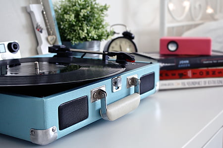 blue and black turntable beside black media player and red speaker place on white table