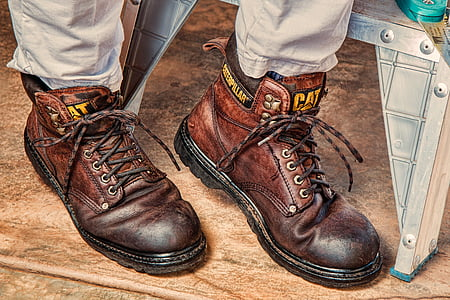 person in brown pants with brown Caterpillar leather work boots