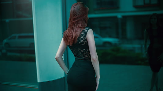 photo of woman in green lace dress standing front of mirror