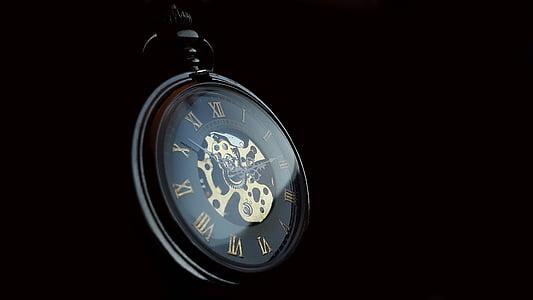 black pocket watch with black background