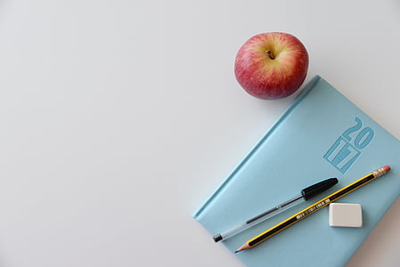 apple beside teal book and pencil