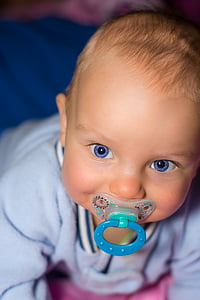 close up photo of baby biting blue pacifier