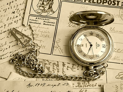 silver-colored pocket watch on white printed papers
