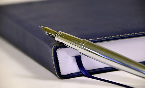 silver fountain pen on top of black leather covered book