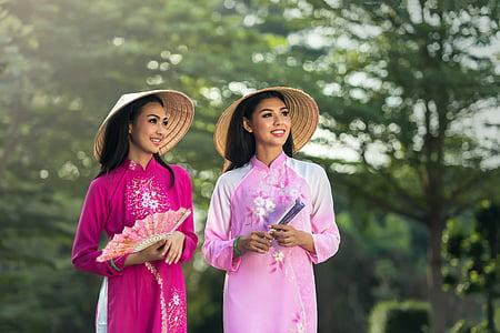 two women in pink cheongsam dresses during daytime