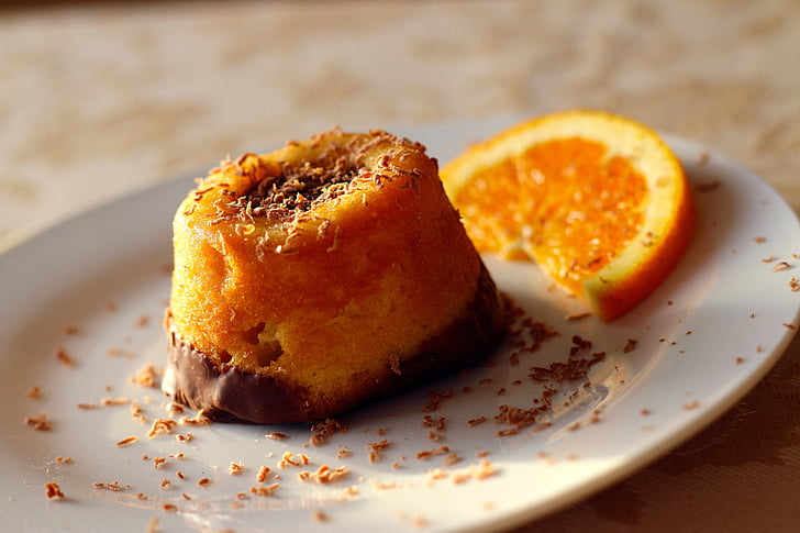 plate of orange chocolate pastry beside slide orange citrus fruit