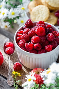 pile of raspberry in white ceramic bowl on table