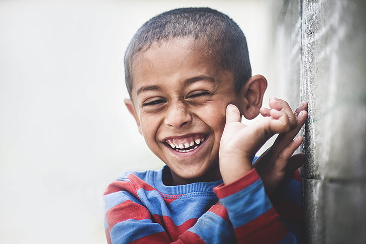 boy smiling leaning on wall