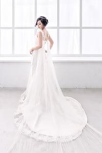 woman wearing white sleeveless bridal gown near window during daytime