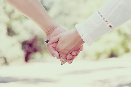 selective photography of couple holding hands