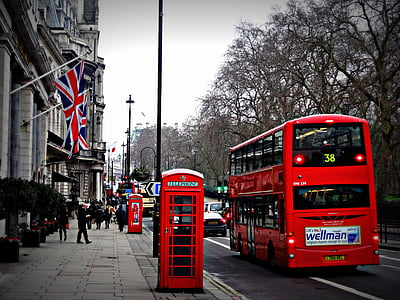 red double decker bus and red phone booth in street