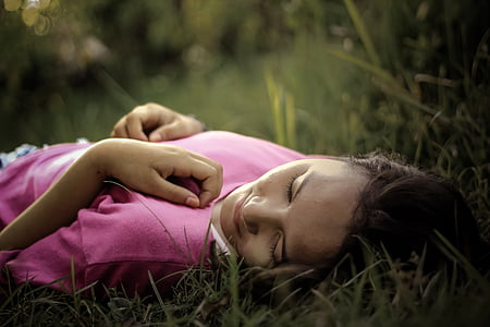 girl wearing pink top lying on grass