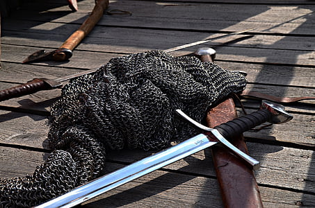 chainmail and long sword on wooden panel