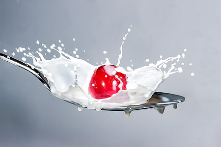 cherry and milk poured on spoon
