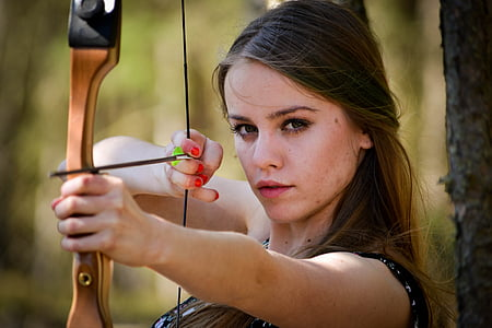 selective focus photography of woman in black top aiming her bow