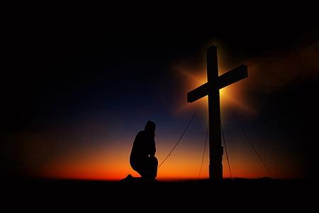 silhouette of man kneeling in front of a cross