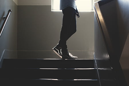 person wearing black skinny jeans and wearing black-and-white Vans sneakers standing on stair